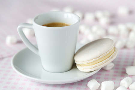 Coffee cup with macaroon on pink napkin