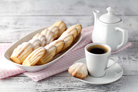 Sugar powdered madeleines on the white plate with coffee