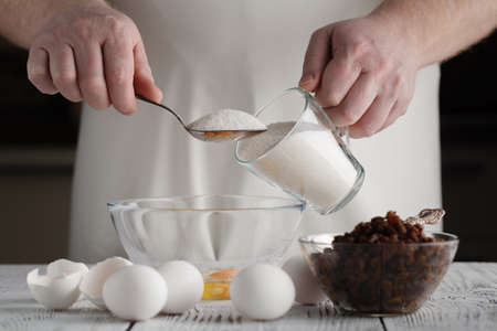 Man adding sugar to cottage cheese in a bowl. Prepares mini cheesecakes with strawberries Stock Photo