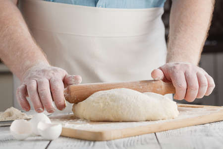 Spreading out cookie dough with wooden rolling pin