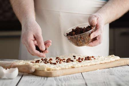 adds: Closeup of man adds raisin into dough.