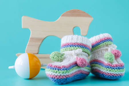 Baby booties with baby rattle sitting on a aquamarine background 写真素材