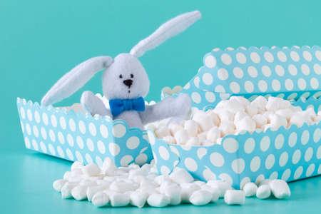 Small round white marshmallows on a aquamarine backgrouns.