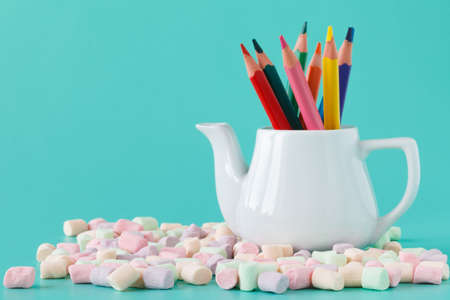 sharpened: Colorful stationery in white kettle on aquamarine background