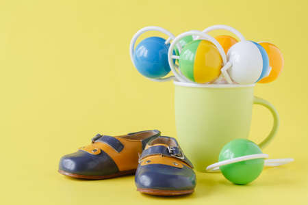 Baby rattle and booties on yellow background
