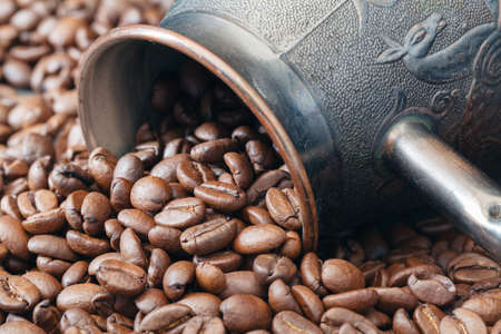 Brass coffee pot on roasted beans