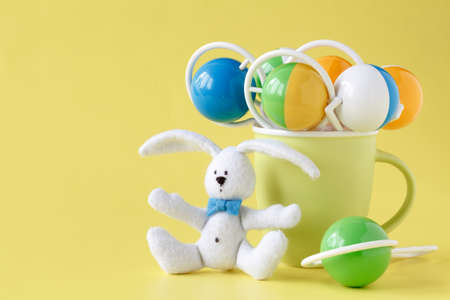 Classic rattle toy with rabbit  on yellow background