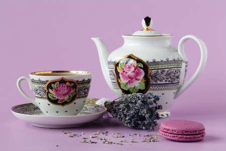 Brezo púrpura con taza de té de porcelana antigua con platillo y té, té de lavanda, día soleado, luz del día Foto de archivo - 77625547