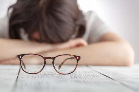 疲れたビジネスウーマン目メガネを彼女の職場は、ビジネス女性感じる落胆メガネを保持して眠りに落ちる 写真素材