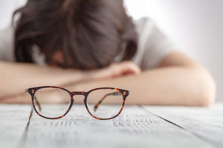 Tired businesswoman falling asleep at her workplace with eyes glasses, The Business Women feel discouraged Holding glasses