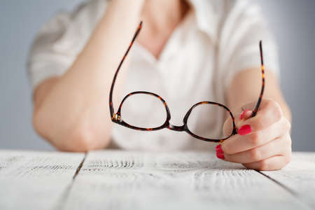 Female hand holding a brown framed glasses