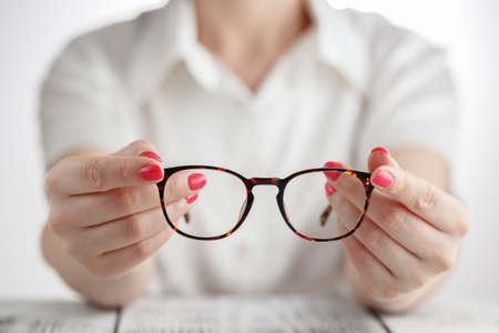 Mano femenina sosteniendo un gafas con marco marrón Foto de archivo - 78976451