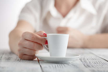 Woman with red nails sitting and holding a hot cup of coffee Stock Photo