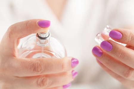 finger pressing the sprayer on perfume bottle Stock Photo