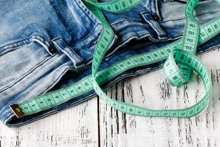 測定テープと木製の背景を持つジーンズ