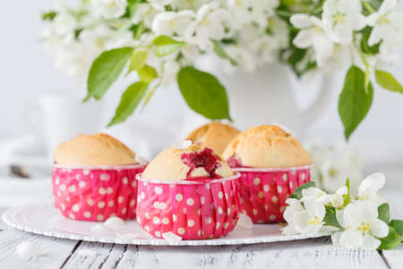 Fresh homemade cupcakes  the apple blossoming branch on a white wooden table Stock Photo