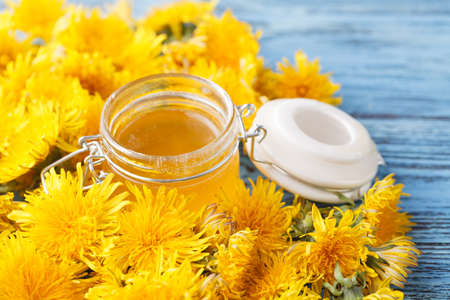 Flower honey in a glass jar and dandelions on a wooden table Stock Photo