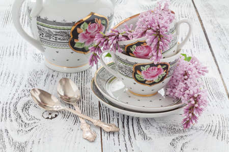 poems: Branch blooming lilac and coffee Cup with milk on a wooden table