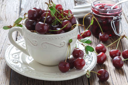 scatters: Fresh cherry berries in a glass on old wooden table background.Selective focus. Stock Photo