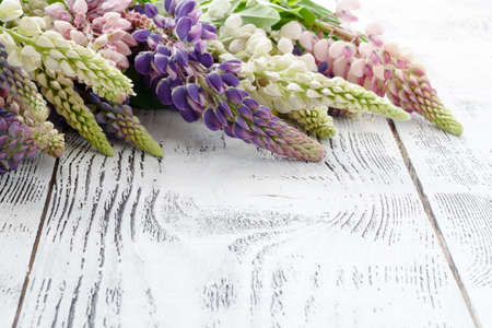 Frame from lupine flowers an old wooden painted background
