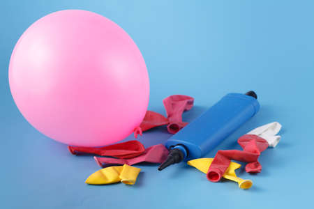 Pile of multiple colorful unblown balloons with a bliue pump over it