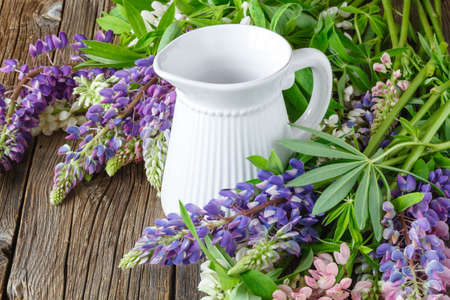 Lupines flowers on wooden and vase Stock Photo