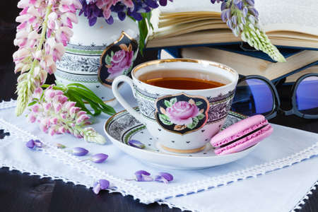 Romantic background with cup of tea flowers and open book over white table Stock Photo