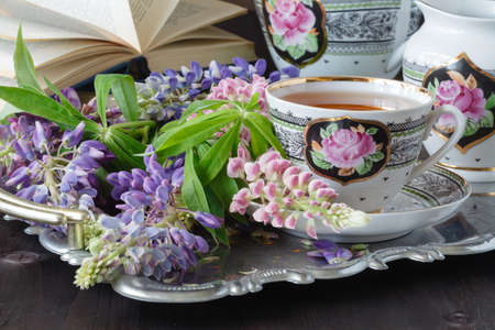 Composition with tea set and bouquet of beautiful spring flowers on tray
