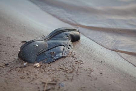 川コートで放棄された挨りだらけの古い靴 写真素材
