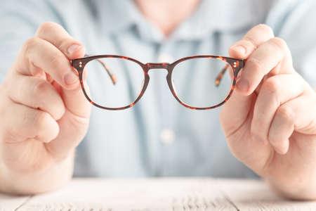 Imagen de detalle: dos manos sosteniendo gafas clásicas Foto de archivo - 81797487