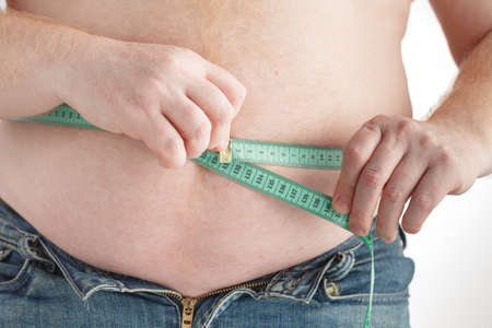 check out: fat man check out his body fat with measuring tape for fat or obesity background