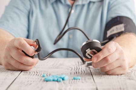 Man Sitting Checking His Own Blood Pressure