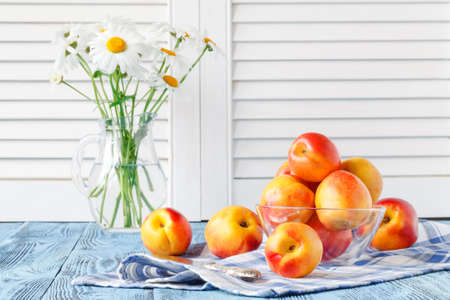 fresh ripe peaches in bowl on blue wooden table and daisy in vase Stock Photo