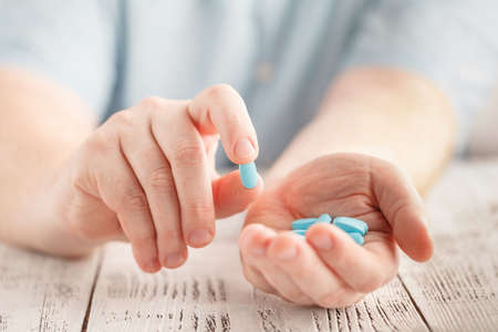 Male hand holding blue pills in palm