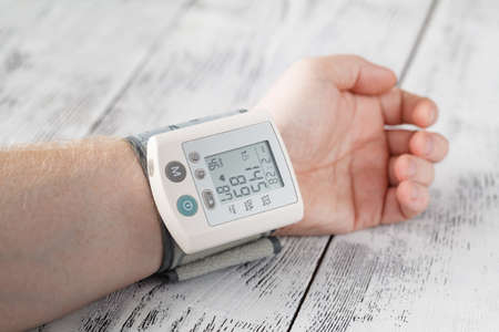 systolic: Man himself measured his own blood pressure on a wrist Stock Photo
