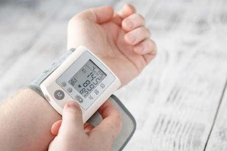 남자 자신이 손목에 자신의 혈압을 측정