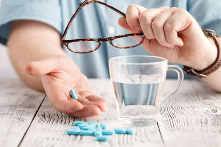 Colored pills and a glass of water in the hands of men. health concept Stock Photo