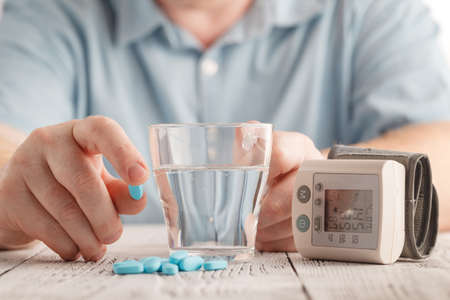 Medical pills against hypertension in hand, equipment for measuring blood pressure