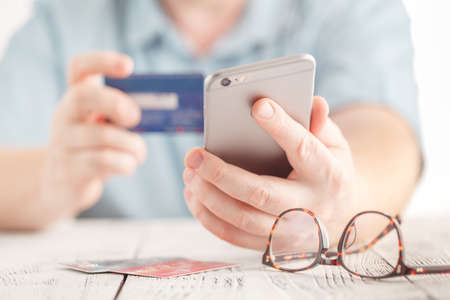 technology transaction: Close up male hands holding credit card and using mobile smart phone for online shopping
