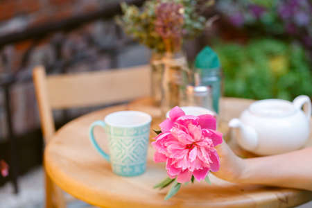 Woman sitting drinking tea at a cafe with flower in hand
