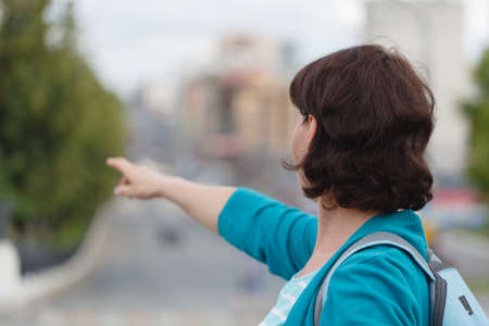 woman show left side hand show forefingerindex finger, correct, pointing, shoot, point up with blur building in the city background
