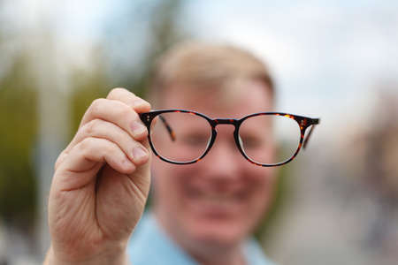 Now I can see you well. Handsome young man holding glasses and looking through them