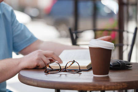 energy work: man reading book with coffee or tea