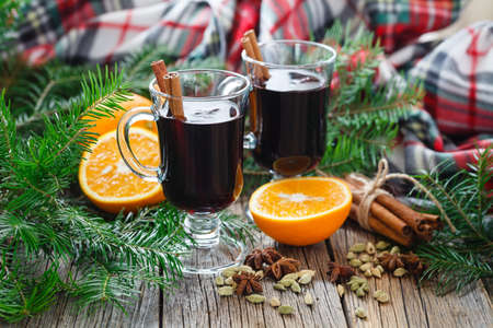 Two glass of hot mulled wine on table with spices