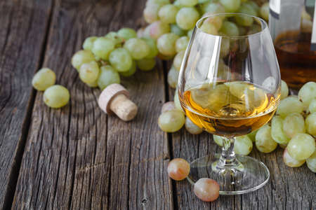 biological vineyard: Glass of brandy with brush of grapes on table, harvest holiday Stock Photo