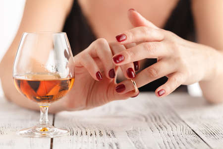 woman is taking off the wedding ring and drink alcohol