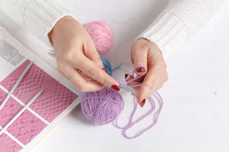 paletas de caramelo: Bolas de hilo de colores. Muestra de punto. Las manos de las mujeres se tejen Foto de archivo