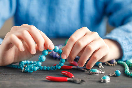 Female hands with colored beads necklace manufacturing