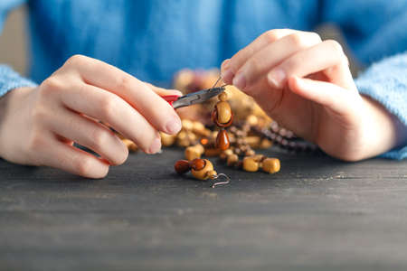 Person making jewelry using wire, chains and beads and other materials with craft tools