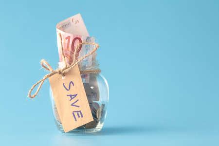 Coins in savings jar full of money Stock Photo